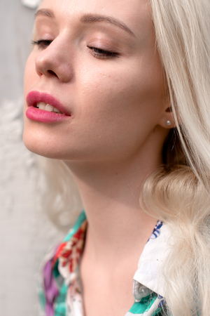 Young european blond woman outdoors portrait. Bright white colors.