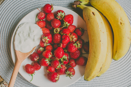erotically: Bunch of bananas and strawberries.   Concept of healthy breakfast.