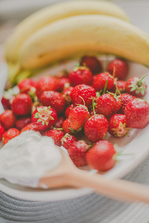 Bunch of bananas and strawberries. Photo toned style Instagram filters. Concept of healthy breakfast.