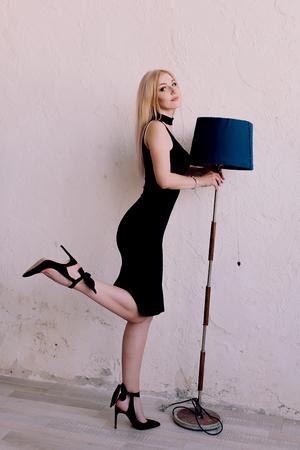 Elegant fashionable sensual blonde middle aged woman in black dress. Fashion retouched shot