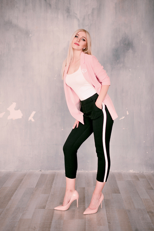Attractive positive middle-aged blond woman wearing pink jacket and pants with trouser stripes with a beautiful smile posing against a receding wall looking directly at the camera Stock Photo