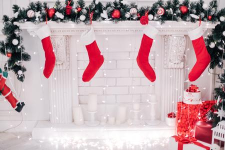 Ein nahes Bild der schön verzierten hellen roten Weihnachtssocken, die an einem Kamin hängen, der auf Geschenke wartet. Standard-Bild