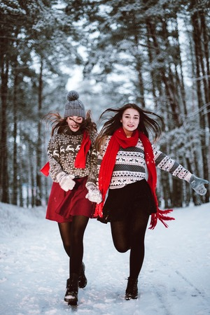 Two young teenage hipster girl friends together.Close up fashion portrait of two sisters hugs and having fun winter time,wearing sweater,best friends couple outdoors, snowy weather