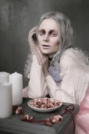 Donker Halloween-portret van de enge slechte zitting van het zombiemeisje als voorzitter en het verzamelen van harten. Conceptuele foto