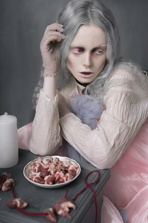 Dark halloween portrait of scary bad zombie girl sitting in a chair and collecting hearts. Conceptual photo