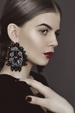 Portrait of young beauty dark hair girl in vintage style dress with beautiful hair and big earrings