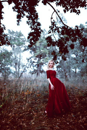 Fashion gorgeous young blonde woman in beautiful red dress in a fairy-tale forest. magic atmosphere