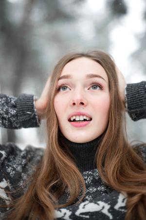 Winter portrait of young beautiful brunette woman wearing sweater. Snowing winter beauty fashion concept.