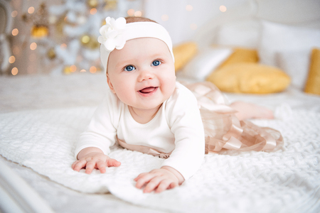 Baby girl wearing cute dress and headband, lies on a white cover in festively decorated room. With surprise watches in the camera, on a background a set of bright fires, soft focus. Warm beige and gold colors Standard-Bild