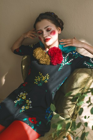 Fashionable beautiful brunette happy girl in a jumpsuit with floral embroidery with color makeup: red cheeks and lips. Granny chic style. Retouched portrait.Conceptual photo