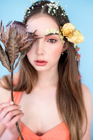 Cosmetics and manicure. Close-up portrait of attractive woman with dry flowers on her face, pastel color, perfect make-up and skin. Fresh, trendy, spring retouched portrait