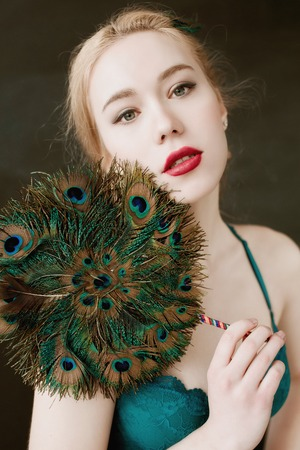 Beautiful girl with bright colored makeup and peacock feather on a black background. Beauty. 免版税图像