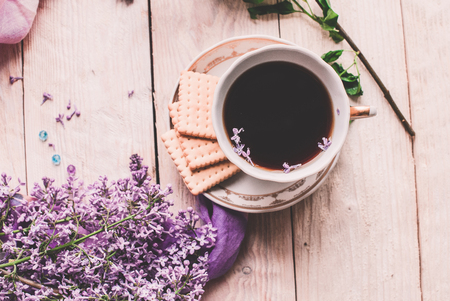 Morning cup of tee, cookies, and lilac flower on wooden table from above. Beautiful breakfast. Flat lay style with copy space