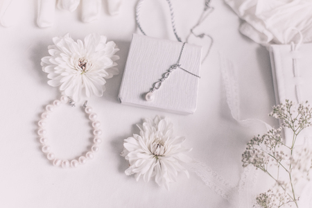 White bridal accessories for wedding background with pearls, white satin ribbons and lace, gloves, bracelet,flat lay for fashion blog, top view