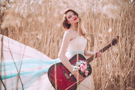 Beautiful romantic european girl with guitar with flowers inside, posing outdoors. Concept of music and nature. Spring time. Fashion retouched shot