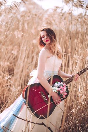 Schönes romantisches europäisches Mädchen mit Gitarre mit Blumen nach innen, draußen aufwerfend. Konzept von Musik und Natur. Frühlingszeit. Moderetuschierte Aufnahme