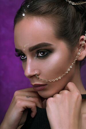 Girl with cool fashionable make-up posing in studio,matte lips and nails,cate eyes,smokey gold eyes, beautiful make up and piercing chain from nose over purple dark background with magic glow. Holiday disco celebration