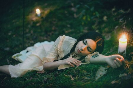 Portrait of a beautiful mysterious woman in the forest Фото со стока