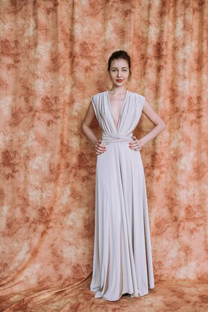 Nice woman with elegant Hairstyle. Brunette Fashion Model Woman wearing Summer Prom long maxi transformer Dress