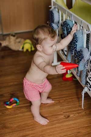 Smiling baby boy playing with toys in his room