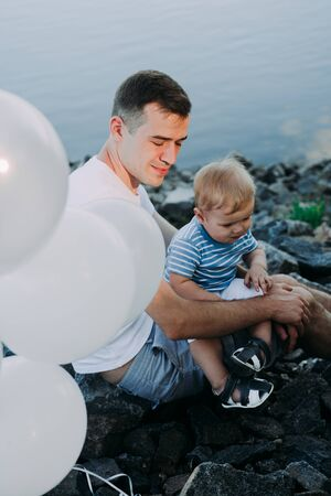 Little boy 1 year old with his father playing with balloons, birthday, summer