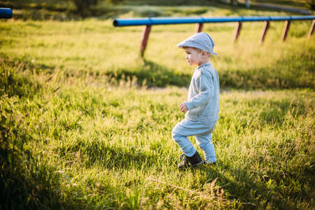 Baby boy 1-2 years old exploring nature in summer, having fun