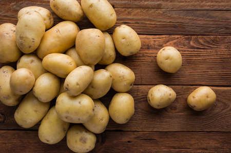 Organic young potatoes raw potato food on wooden background
