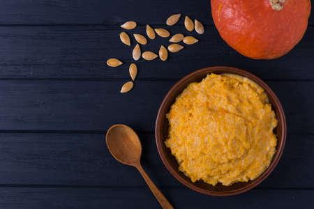 Homemade pumpkin porridge with seeds on wooden background