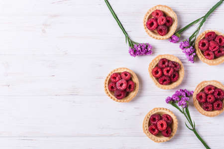 Sweet tartlet with raspberries on white background