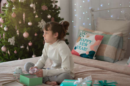 A funny dark-haired girl sits on the bed with gifts, near the Christmas tree. Lettering on the pillow in English Happy New Year! Place for an inscription. Stock Photo