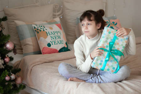 A funny dark-haired girl sits on the bed with gifts, near the Christmas tree. Lettering on the pillow in English Happy New Year! Place for an inscription. 版權商用圖片