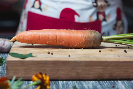 unwashed: Carrots unwashed on a chopping board. Kitchen table, women in apron