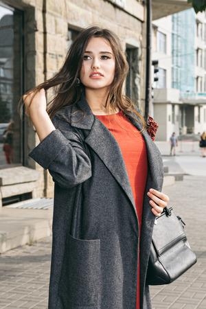 Fashion portrait of beautiful sexy woman Wearing a fashionable orange dress, gray coat. Posing on a city street Stock Photo