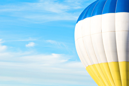 carnival ride: Multicolor (blue, white, yellow) air balloon in blue sky with cloud