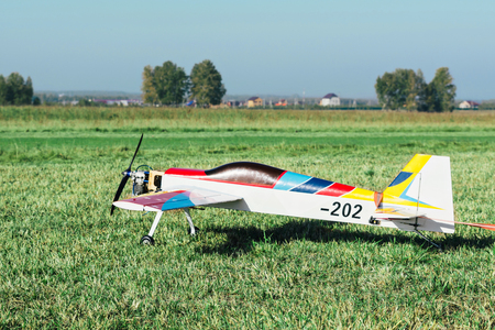 Homemade radio control toy aircraft with motor parked on a grassy field