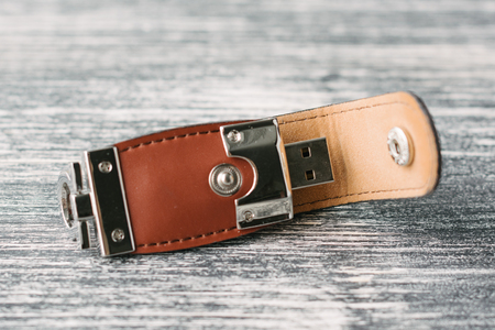 storage device: storage device with leather covering. Brown leather USB stick isolated on black and white wooden background. Creative USB flash drive