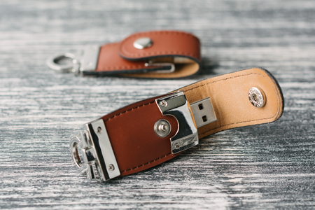 Two storage devices with leather covering. Brown leather USB sticks isolated on black and white wooden background. Creative USB flash drives Stock Photo