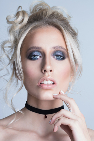 Portrait of a beautiful young blonde woman. Girl with fashion hairstyle and makeup. Trendy black velvet choker