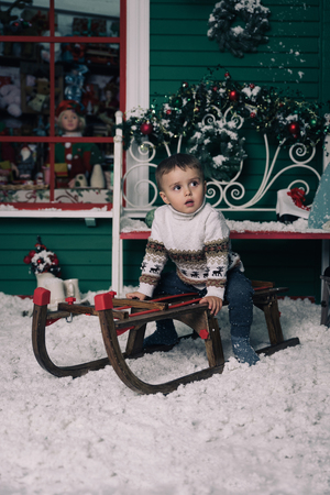 window bench: Little boy enjoying sleigh ride. Child sledding on sledge. Green wall with a window, bench is decorated with a Christmas wreath. Studio shoot