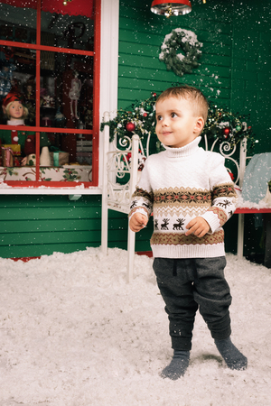 window bench: Little boy standing on snow. Cute boy wearing christmas style sweater. Green wooden wall with a window, bench is decorated with a Christmas wreath. Studio shoot