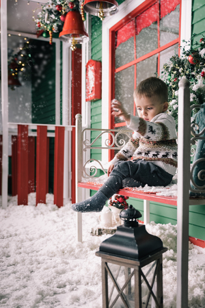 window bench: Little boy sitting on bench. Cute boy wearing christmas style sweater. Green wooden wall with a window, bench is decorated with a Christmas wreath. Studio shoot Stock Photo