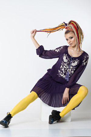 Pretty woman with bright colors dreadlocks. Women in a purple dress with a white ornament and yellow tights sitting on cube. Studio shoot Stock Photo
