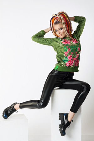 Pretty woman with bright colors dreadlocks. Beautiful sexy woman sitting on a cube, wearing a stylish fashionable black tight pants eco leather and green sweatshirt Stock Photo