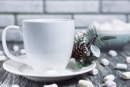 Drink in a white ceramic cup with zephyr on wooden table. Decorative pine branch with the cone on plate, saucer