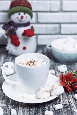 Drink in a white ceramic cup with zephyr on wooden table. Red poinsettia flower on plate, saucer. Snowman on background