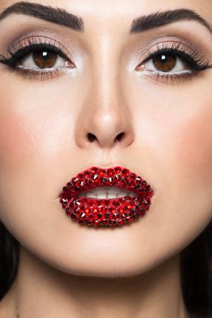 Le donne affrontano con cristalli Swarovski sulle labbra. Donna bruna con acconciatura di moda e make-up vacanza con gemme rosse. Archivio Fotografico