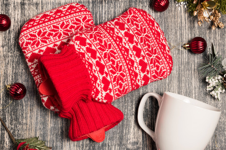 tight filled: Hot water bottle on the background. Red bag with water on wooden table