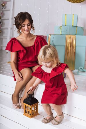 decorate: Women playing with girl near Christmas tree. Portrait of mother and daughter in identical red dresses.