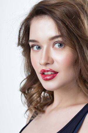 smoky black: Studio portrait of a beautiful young woman. Fashion Makeup Model with perfect makeup, red lips and smooth, clean skin. Highlighter