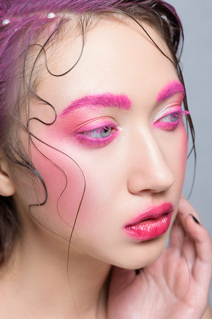 Woman with creative pink colorful make-up. Beautiful brunette girl with pink brows and lashes, glossy lips, wet hair with perl